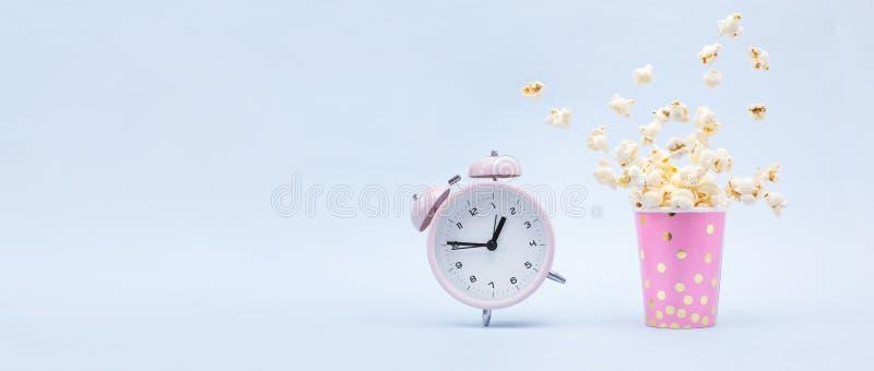 在一块明亮的玻璃和一个敲响的闹钟的飞行的玉米花在蓝色背景 乐趣概念的时刻 库存照片