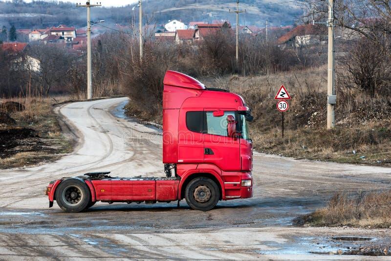 在一条农村乡下公路的红色半卡车 免版税库存图片