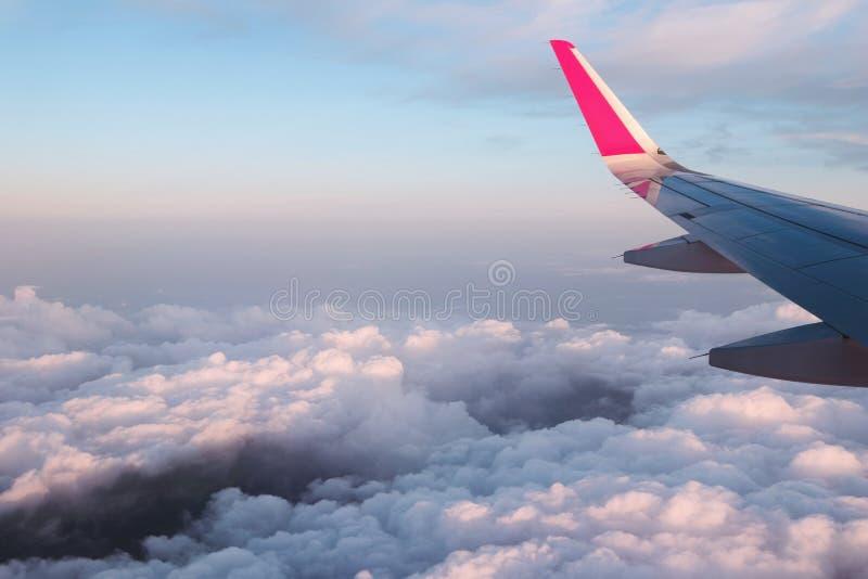 在一次飞行的飞机翼在日落期间的云彩上 库存照片