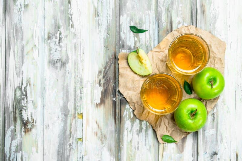 在一玻璃杯的苹果汁在一个木板 免版税库存图片