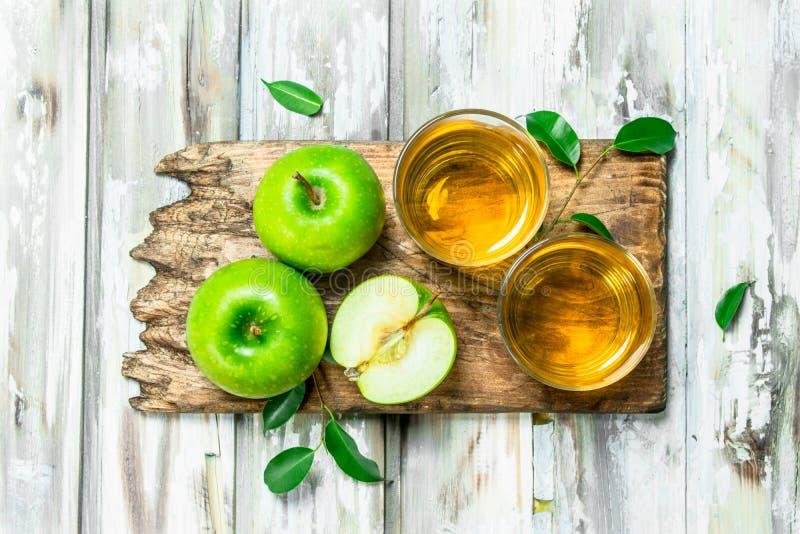 在一玻璃杯的苹果汁在一个木板 图库摄影