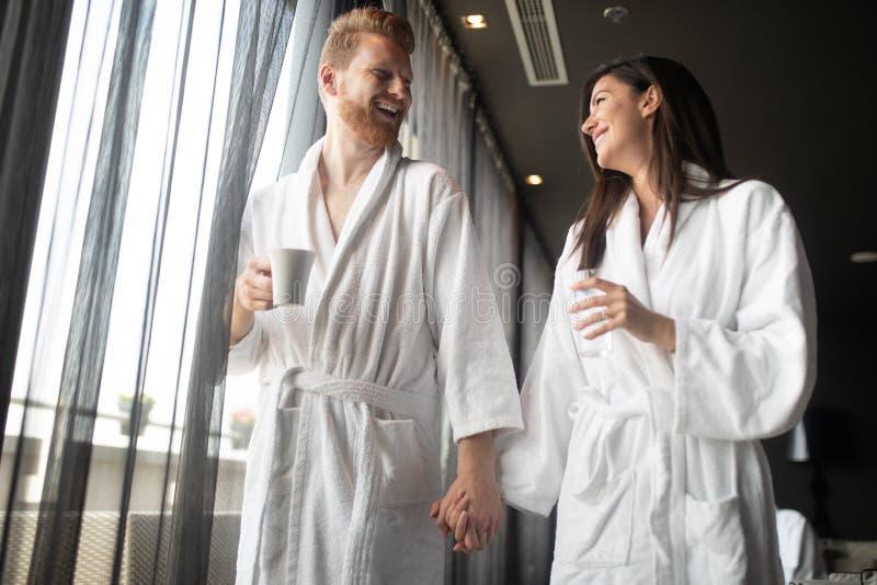 在一起喝咖啡的白色浴巾的愉快的年轻夫妇 旅馆,旅行,关系概念 库存图片