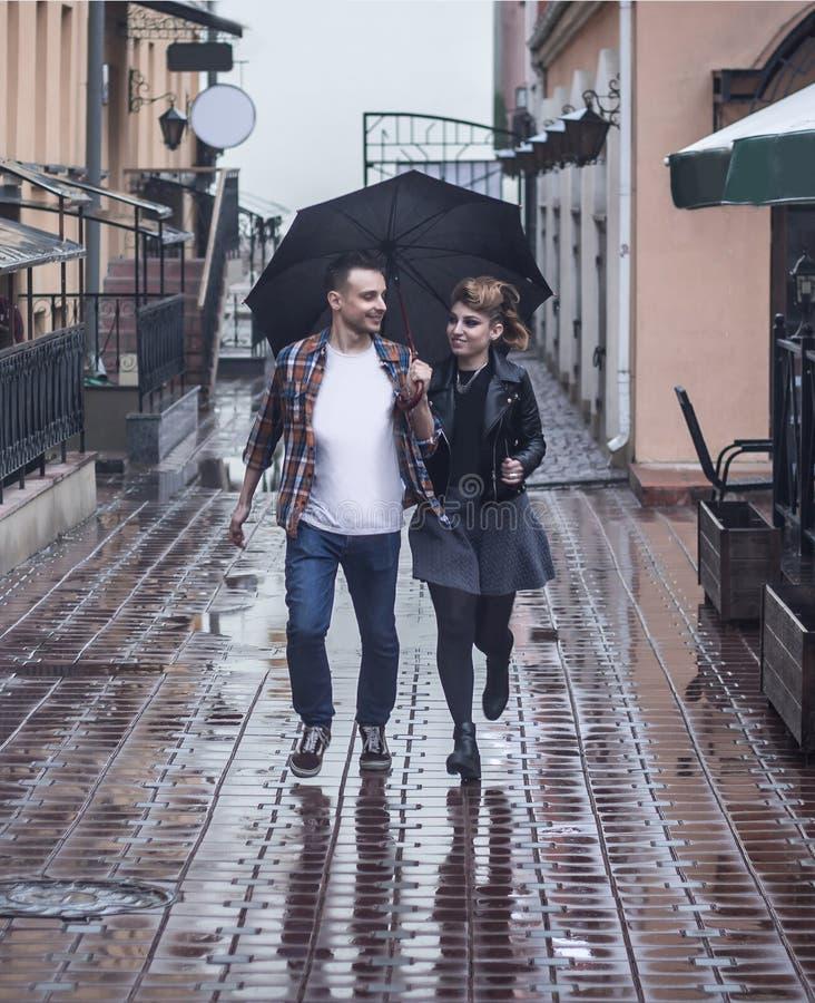 在一起爱奔跑的年轻夫妇在一把伞下在一下雨天 免版税库存图片