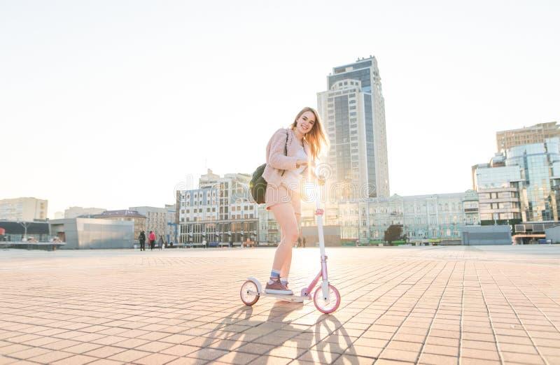 在一辆桃红色反撞力滑行车的女孩乘驾在街道上在日落、微笑和看看的背景中照相机 库存图片
