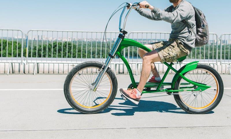 在一辆时髦的绿色自行车的步行在城市附近 便服的一个骑自行车者在沥青骑城市自行车 走的自行车 图库摄影