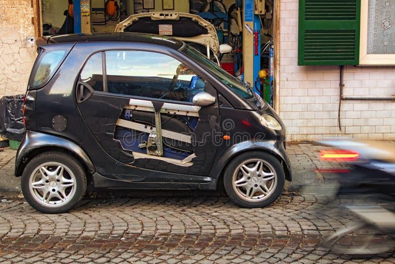 在事故期间,车门被咬嚼了 一个小汽车车间专门研究有严重事故的定象汽车 免版税库存照片