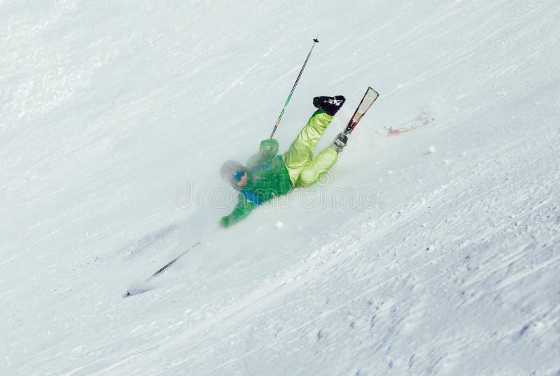 在从山的下降期间滑雪者跌倒了 免版税库存照片
