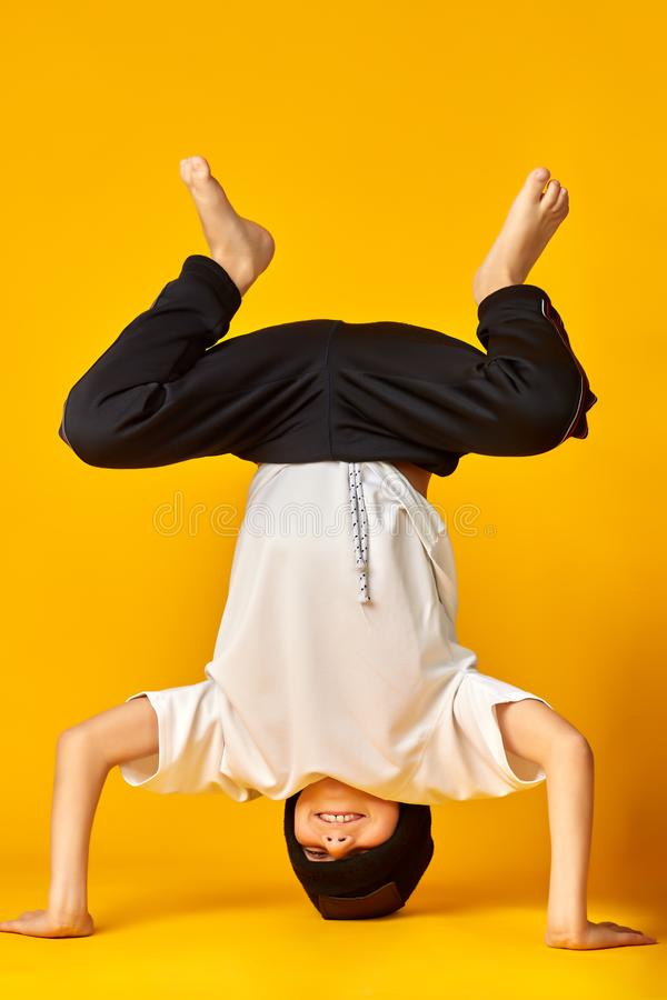 在他的头的英俊的断裂舞蹈家身分在黄色背景的演播室 免版税库存照片