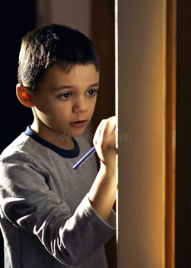 在他的室墙壁上的男孩图画  免版税图库摄影