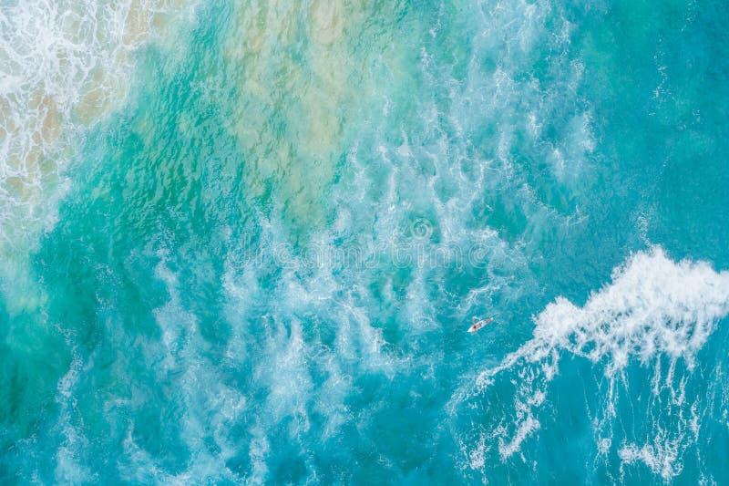 在他的冲浪板的冲浪者划船往海浪 免版税库存图片