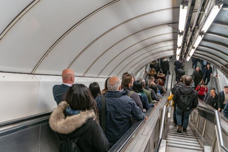 在伦敦地铁的银行驻地,人们在下班时间使用自动扶梯 库存图片