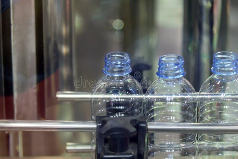 在传送带的塑料瓶在饮用水工厂 免版税库存图片