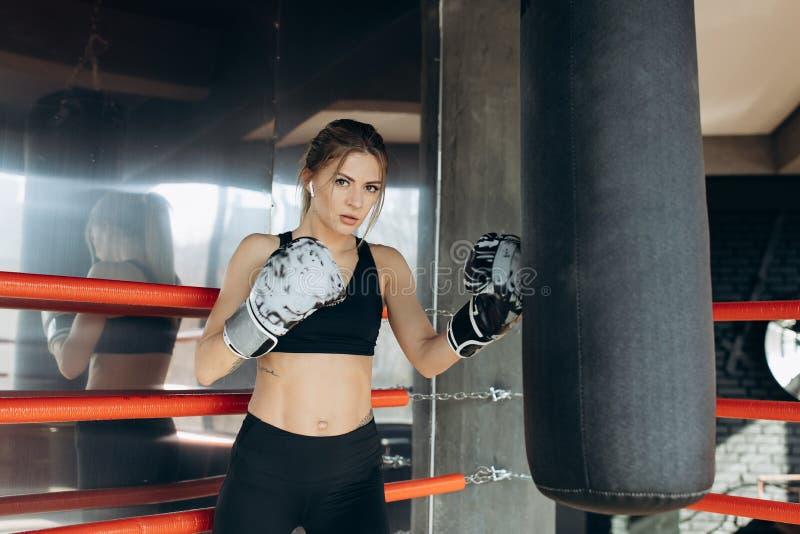 在健身演播室剧烈力量适合身体kickboxer系列的Kickboxing妇女训练吊袋 免版税图库摄影
