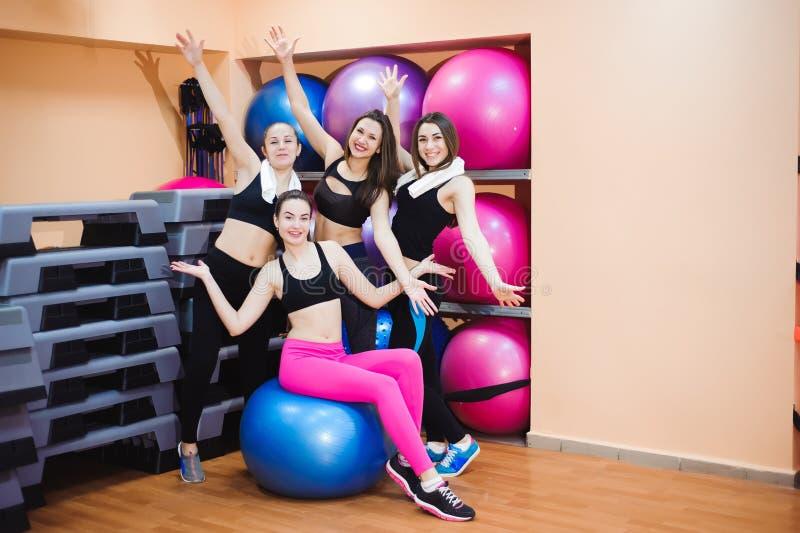 在健身房训练的小组愉快的妇女使用设备 背景黑体字四个女孩编组隐藏的查出的纵向摆在 免版税库存照片