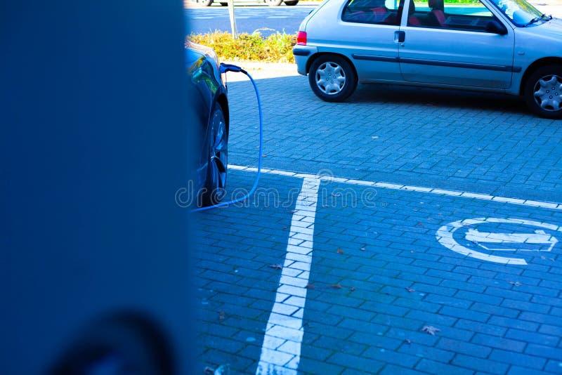 在停车处停车场 充电一辆电车与电 在停车场的一台暗藏的照相机在汽车后 免版税库存照片