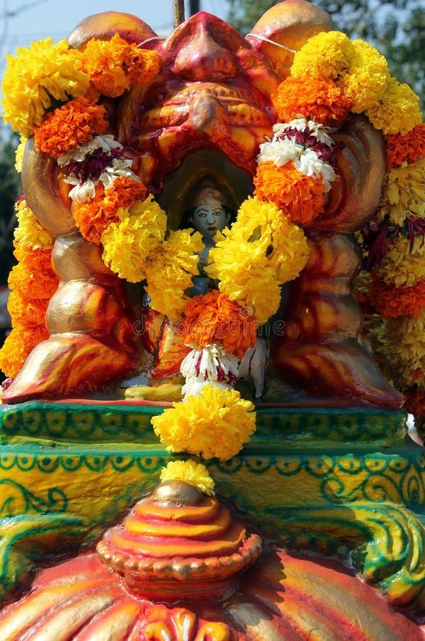在印度寺庙的雕象有橙色和黄色万寿菊Tagetes花的欢乐装饰的 库存照片