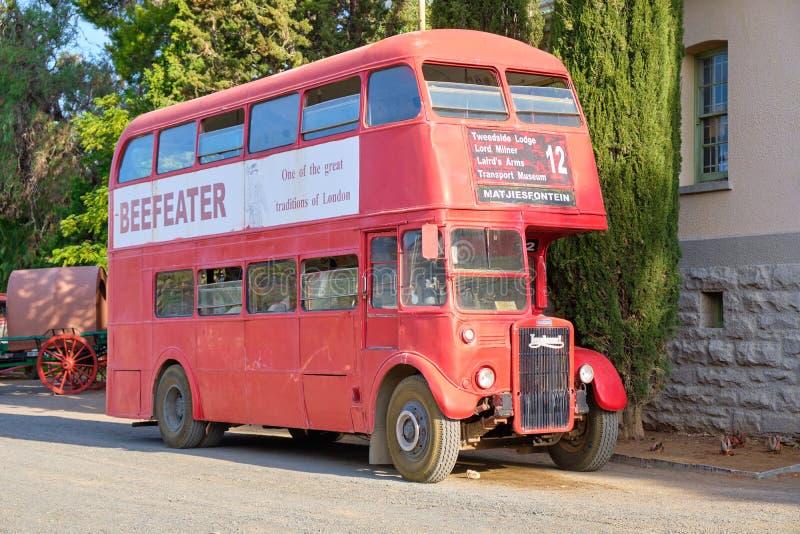 在南部非洲的干旱台地高原的红色公共汽车 免版税库存照片