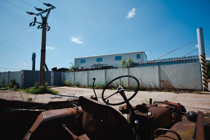 在后院-钢葡萄酒机械生锈的片断的被放弃的拖拉机  免版税库存图片