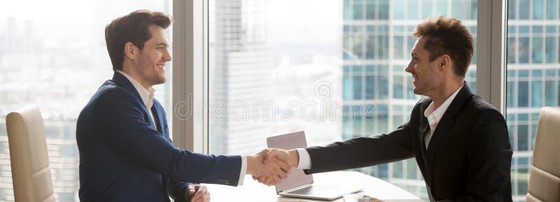 在坐在办公桌的衣服握手的水平的图象商人 库存图片