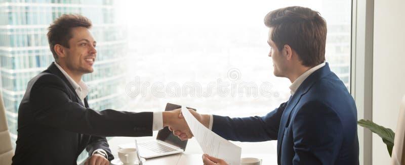 在坐在现代办公室的衣服握手的水平的图象商人 免版税库存照片