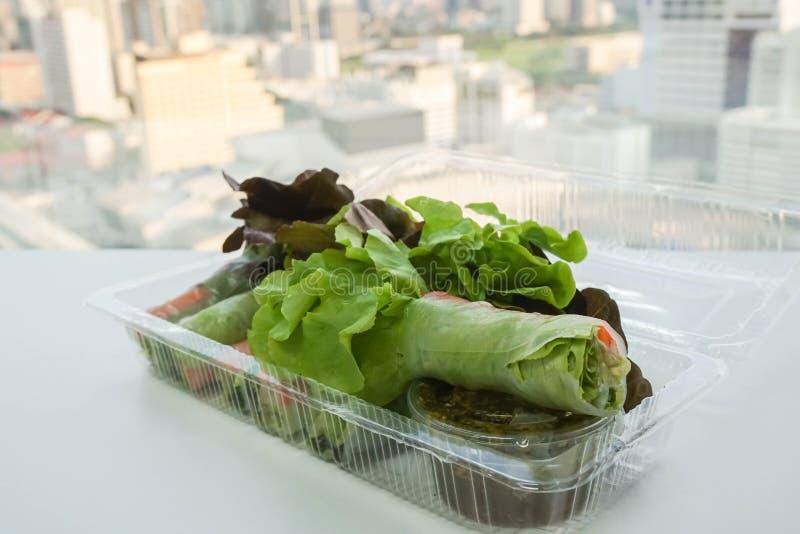 在塑料盒的健康菜沙拉卷 库存图片