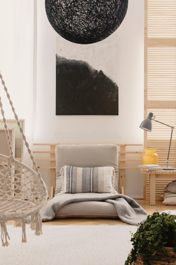 在墙壁上的抽象黑白绘画在与蒲团床的明亮的卧室内部和花瓶和灯在床头柜上 免版税库存图片