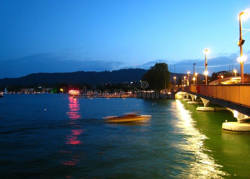 在夏天天气的美丽夜视图与在苏黎世湖的一只快艇 免版税库存照片