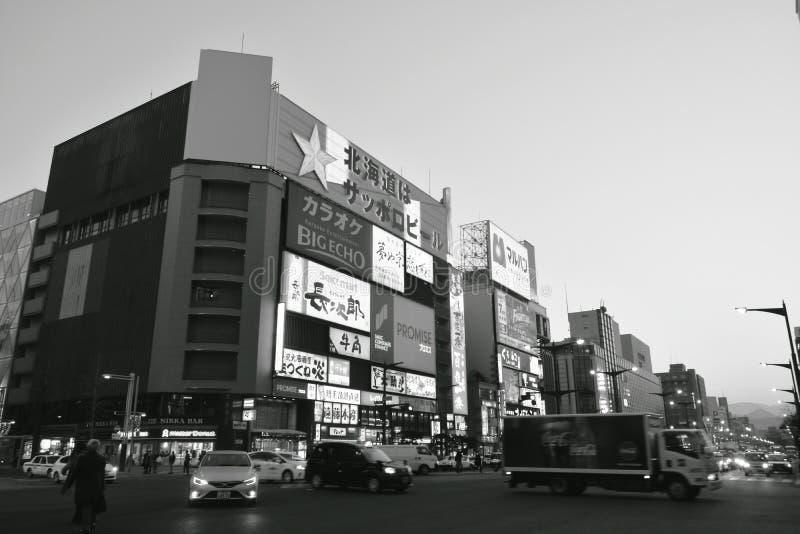 在大厦后的日落在Tanukikoji街道在日落的Supporo 免版税图库摄影