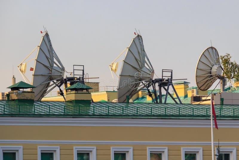 在大厦屋顶特写镜头的卫星抛物面天线在晴朗的早晨 库存图片