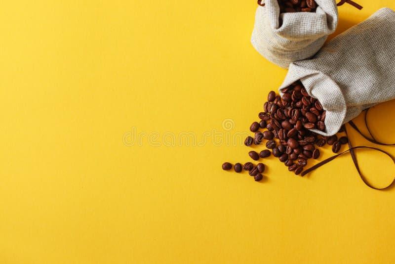 在大袋的咖啡豆在与拷贝空间的黄色背景您的文本的 库存照片
