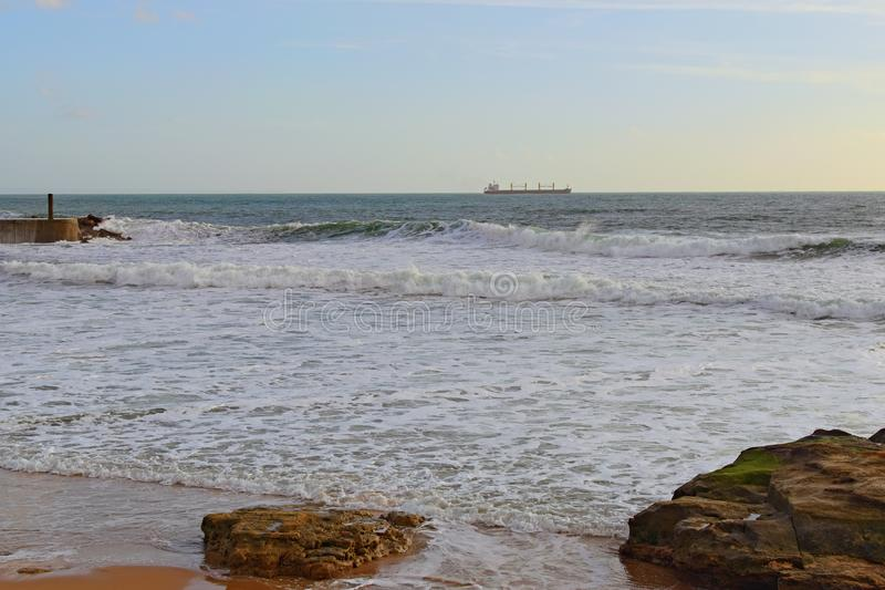 在大西洋的岸的日落在卡斯卡伊斯,葡萄牙附近的 在天际的油槽 库存照片