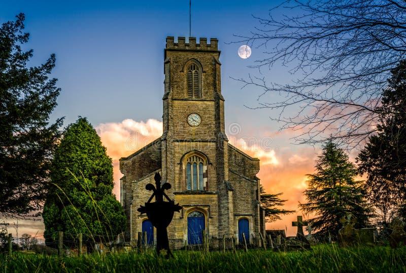 在天空的月亮在教会钟楼后的日落在Corsley,威尔特郡,英国 库存照片