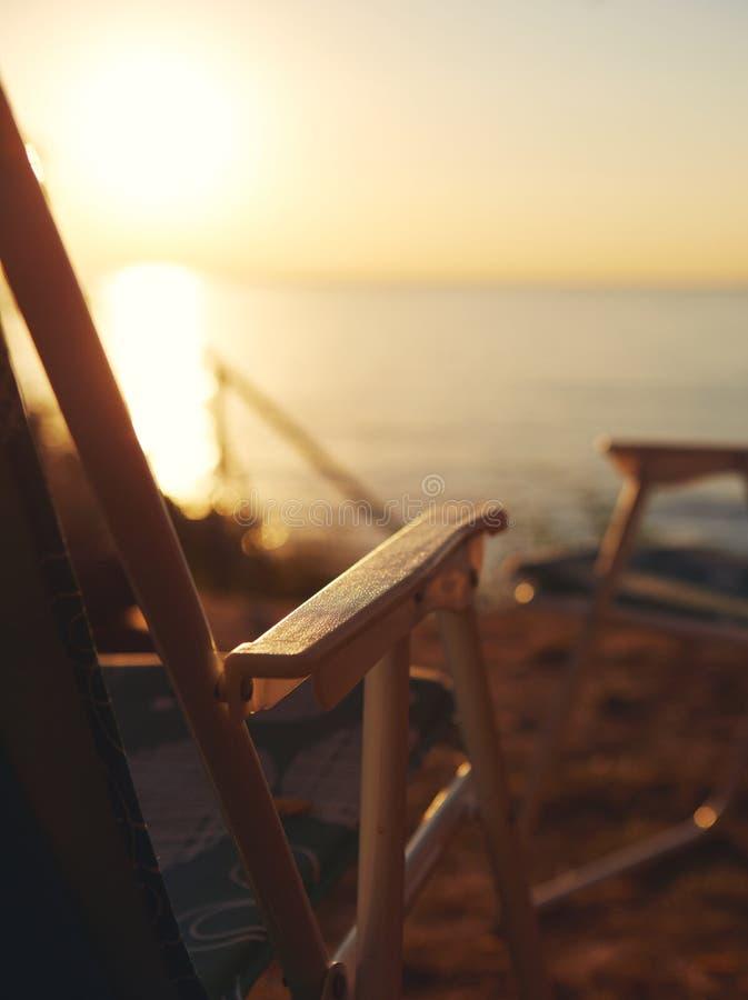 在天蓝色的海的海岸的海滩睡椅有日落天空背景 库存照片