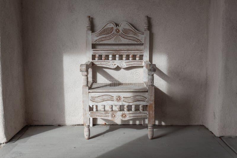 在多孔黏土适当位置的老被雕刻的椅子,美国西南,圣塔菲 免版税库存图片