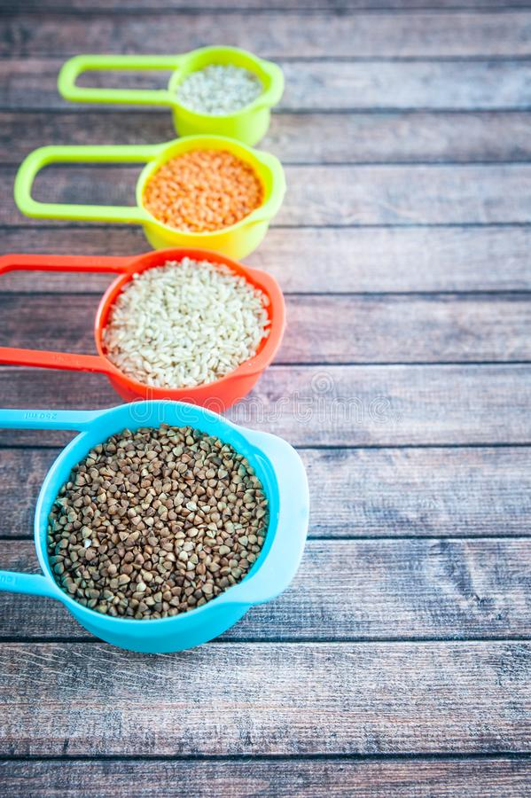 在多彩多姿的容器、燕麦粥荞麦、大麦和米的汇集谷物 库存图片