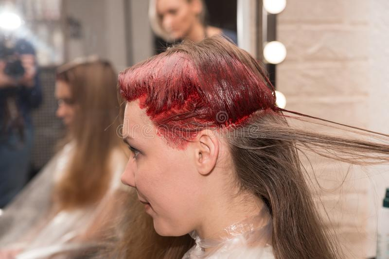 在头发染色期间的girl's半色头在 hairdresser's沙龙的镜子被反射 免版税库存图片