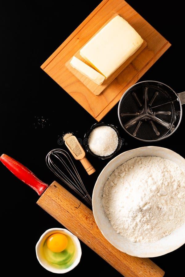 在头顶上食物配制概念射击了为揉面团的厨房工具面包店、比萨或者面团的在黑背景与拷贝 库存照片