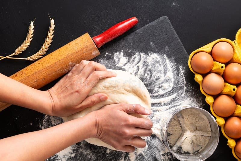 在头顶上食物配制概念射击了面包店、比萨或者面团的揉的面团在与拷贝空间的黑背景 免版税图库摄影