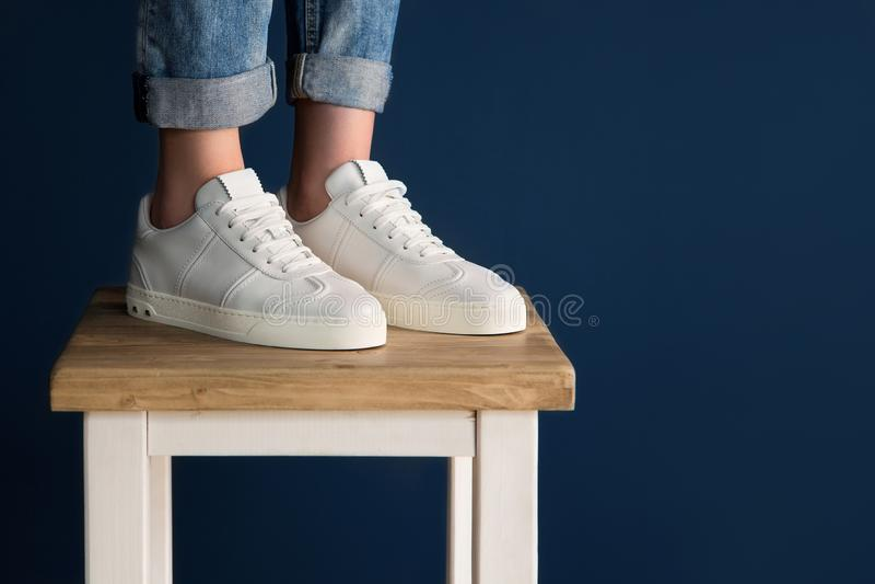 在女孩的腿的白色运动鞋 库存图片