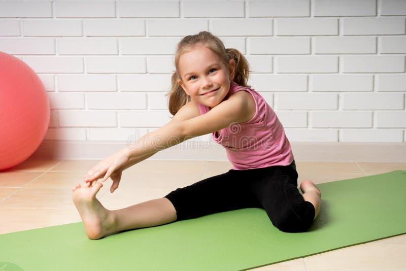 在家做在席子,儿童的体育和瑜伽的快乐的女孩体育锻炼 免版税库存图片