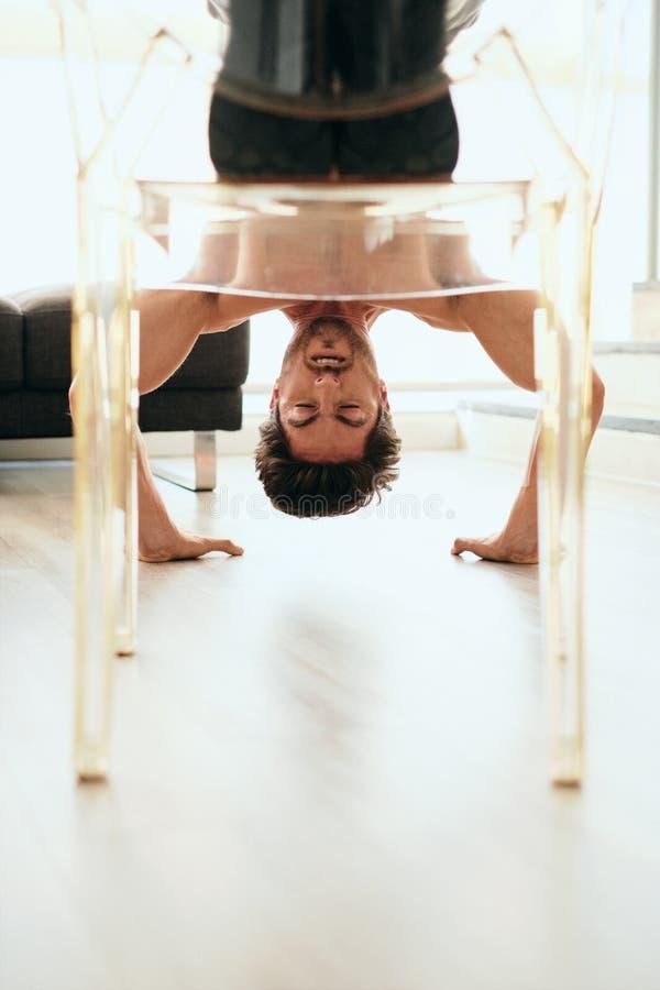 在家做倾斜的俯卧撑的成人人训练胸口肌肉 免版税库存照片