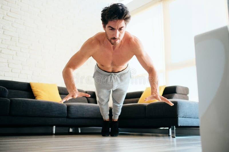 在家做易爆的俯卧撑的成人人训练胸口肌肉 免版税库存图片