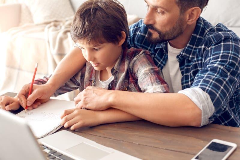 在家坐在桌上的父亲和儿子做拿着男孩的手文字解答特写镜头的任务爸爸 免版税图库摄影