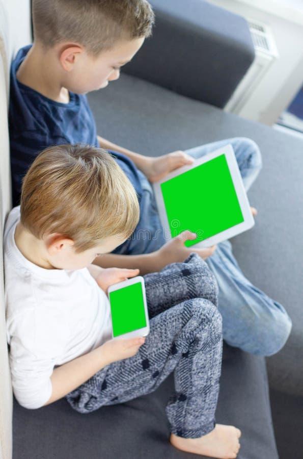 在家坐和使用片剂和流动智能手机有绿色屏幕的男孩 免版税图库摄影