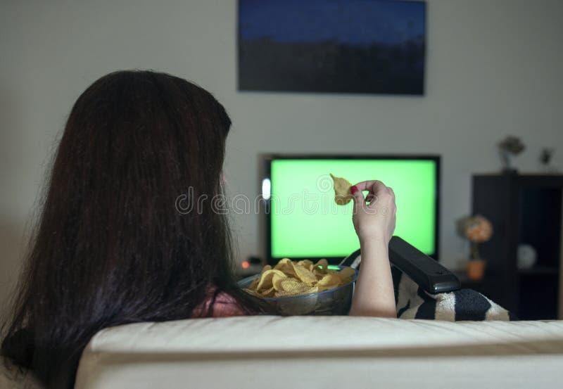 在家坐松弛晚上的深色的妇女吃薯片和看电视,一个绿色屏幕 免版税图库摄影