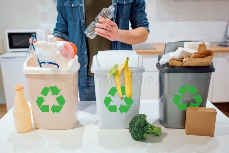 在家排序的废物 回收 投入塑料瓶的人在垃圾桶在厨房里 库存图片