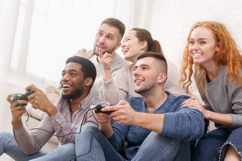 在家打电子游戏的激动的朋友 免版税库存图片