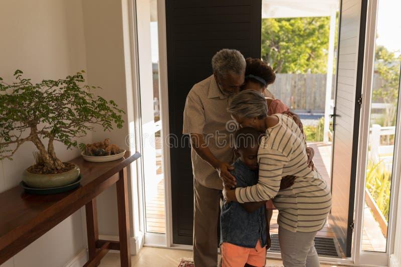 在家拥抱他们的孙的祖父母 免版税库存图片