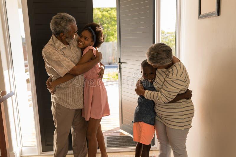在家拥抱他们的孙的祖父母 库存图片