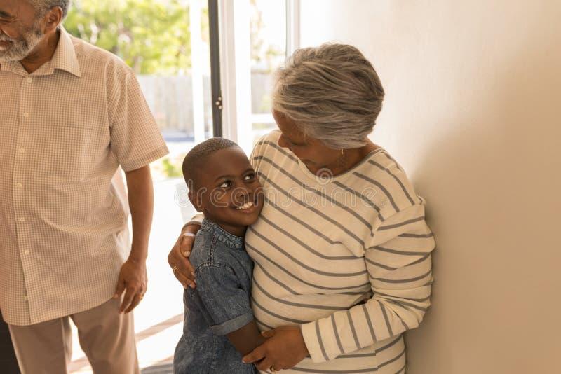 在家拥抱她的孙子的祖母 免版税库存图片